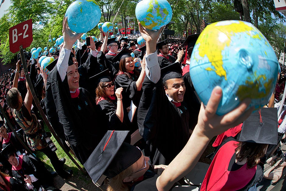 Harvard Kennedy School students cheer and hold up inflatable globes during Commencement. Brooks Canaday/Harvard University