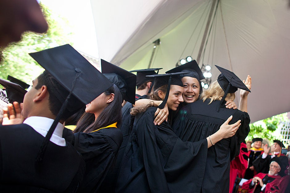 Students share a hug after receiving their degree. Justin Ide/Harvard Staff Photographer