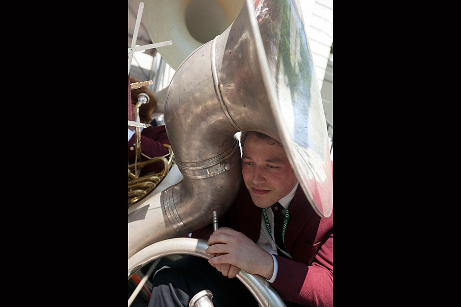 Harvard Band member Duncan Watts '12 curls up under his sousaphone during Commencement. Kris Snibbe/Harvard Staff Photographer