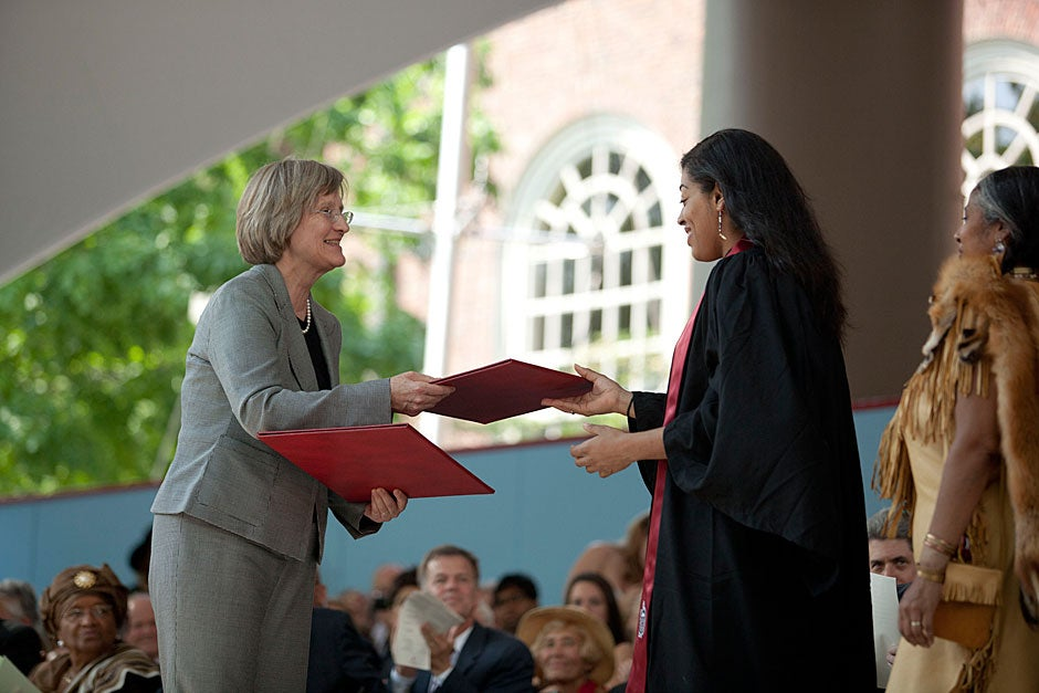 Tiffany Smalley '11 receives a special degree from President Drew Faust, awarded posthumously to Joel Iacoomes, Harvard College Class of 1665, during Harvard's 360th Commencement. On the right is Cheryl Andrews-Maltais, chairwoman of the Wampanoag Tribe of Gay Head (Aquinnah). Kris Snibbe/Harvard Staff Photographer