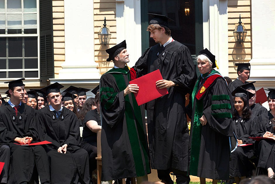 Adams House co-Masters Sean and Judith Palfrey (right) award a degree to David Wakulich '11 during the graduation ceremony at Adams House. Kris Snibbe/Harvard Staff Photographer