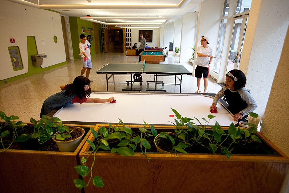 Mara (left) and friend Autumn play air hockey while Currier students play ping-pong in the lower level lounge. Rose Lincoln/Harvard Staff Photographer