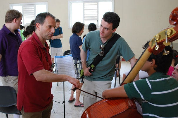 Harvard-Radcliffe Orchestra director Federico Cortese (left) works with students at the Escuela de Arte Benny Moré in Cienfuegos, Cuba.