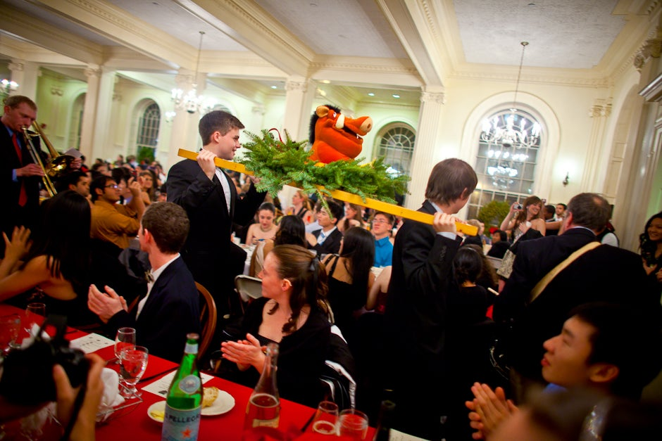 """Students cheer and sing as a """"boar head"""" is carried around the dining hall followed by a musical tribute to the holidays. The House has been specially prepared for the holidays and the festive dinner. Justin Ide/Harvard Staff Photographer"""