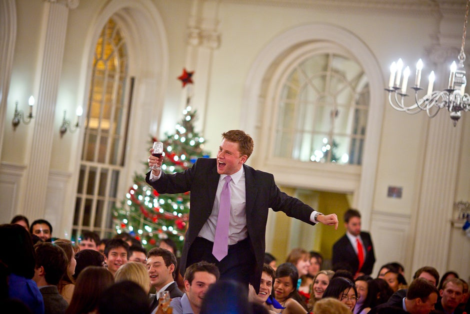 Mark Isaacson '11 toasts his fellow Kirkland House residents and House Masters during a winter dinner celebration inside the dining hall. Justin Ide/Harvard Staff Photographer