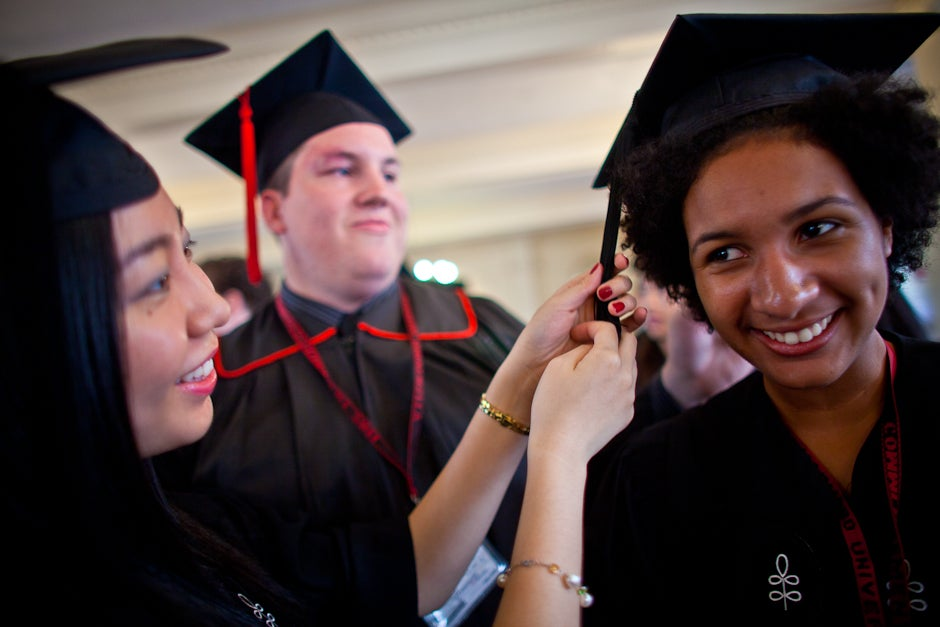 Seniors Cathy Sun, Brad Paraszczak, and Marina Magloire try on their caps. Justin Ide/Harvard Staff Photographer