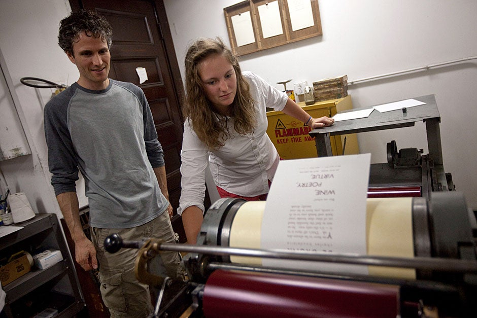 Zachary Sifuentes (left), visiting lecturer on visual and environmental studies and resident tutor in poetry at Adams House, watches Kathryn Reed '13 print a poem by Charles Baudelaire inside the Bow and Arrow Press at Adams House during Open Press Night. Kris Snibbe/Harvard Staff Photographer