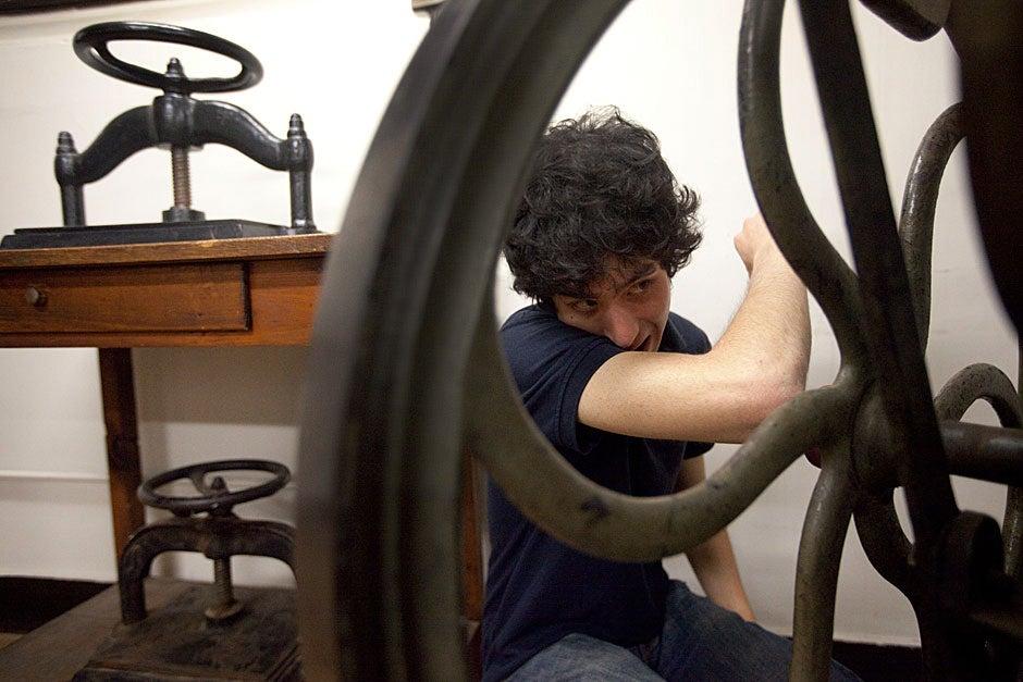Student press master Daniel Gross '13 explores the historical presses inside Bow and Arrow Press. Kris Snibbe/Harvard Staff Photographer