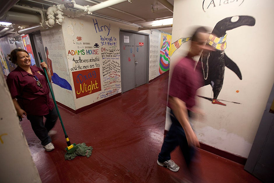 """Alma Ortiz mops the floors of the tunnels while Edward Gorey's """"Doubtful Guest"""" looks on. Kris Snibbe/Harvard Staff Photographer"""