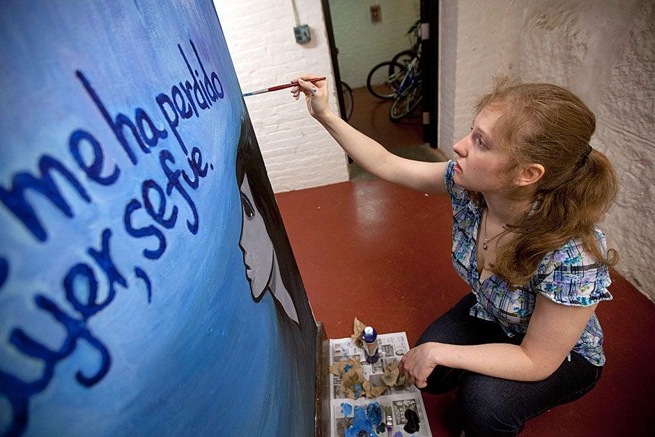 Lidiya Petrova '11 paints a blue unicorn inside the tunnels. Kris Snibbe/Harvard Staff Photographer