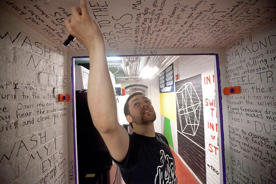 Joe Poirier '11 paints lyrics from a Bob Dylan song inside the Adams House tunnels. Kris Snibbe/Harvard Staff Photographer