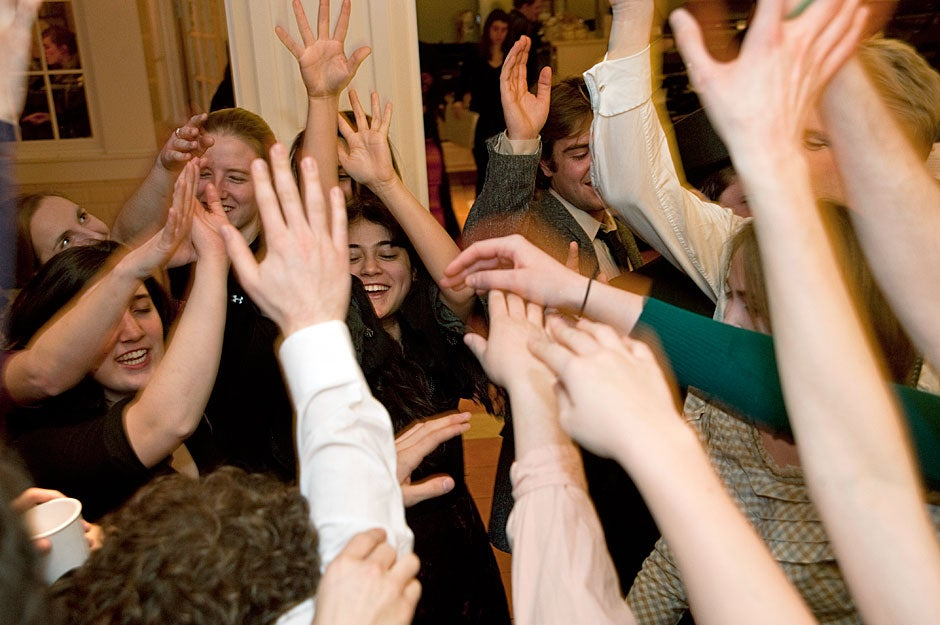 """In a show of camaraderie, Dunster House Opera Society members raise hands in a group salute before going onstage to perform Johann Strauss' """"Die Fledermaus."""" Jon Chase/Harvard Staff Photographer"""