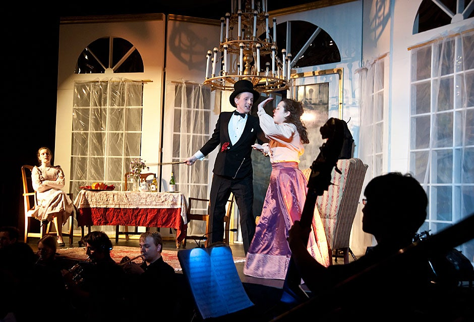 """Framed by a bass player in the orchestra, the Dunster House Opera Society performs Johann Strauss' """"Die Fledermaus"""" with Ben Nelson '11 and Bridget Haile '11 in the lead roles at center stage. Jon Chase/Harvard Staff Photographer"""