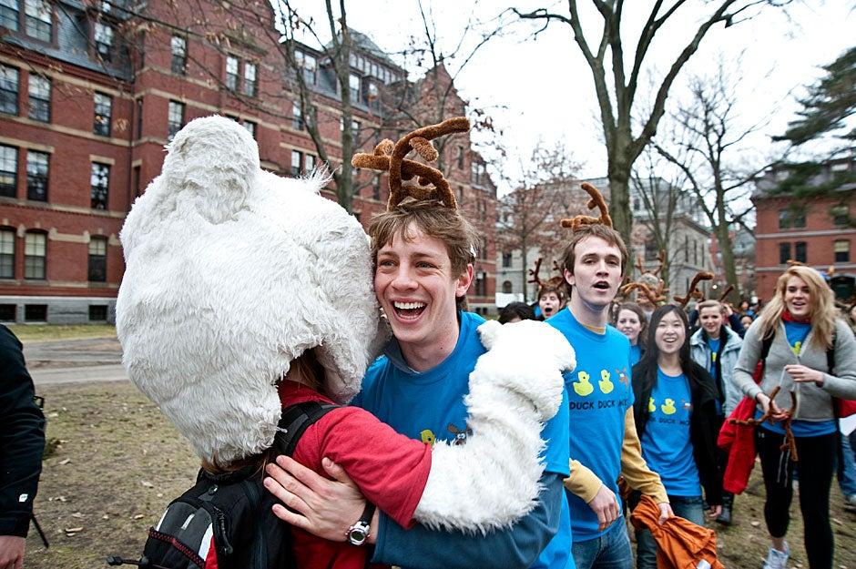 Michael Baskin '11 of Dunster House gets a hug from the Pforzheimer bear in the Yard on Housing Day. Jon Chase/Harvard Staff Photographer