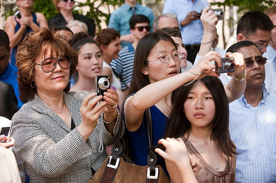 Dunster House families have their own photo op as they capture graduates receiving diplomas at the House ceremony following Commencement Morning Exercises. Jon Chase/Harvard Staff Photographer