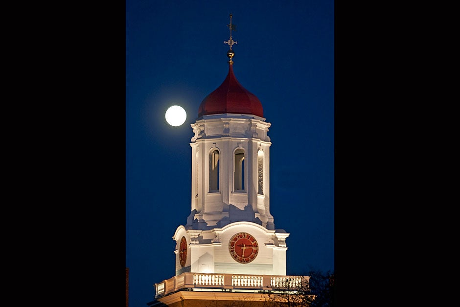 A full moon rises behind the Dunster House tower. Jon Chase/Harvard Staff Photographer
