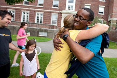 Acky Uzosike '13 (right) is welcomed back to campus by Allston Burr Resident Dean Jill Constantino at Cabot House during move-in day. Constantino's husband, Michael Baran, and their daughter, Rio, age 7, are in the background.