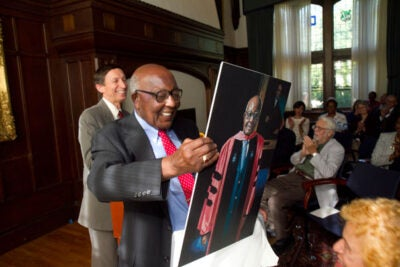 Preston N. Williams, Houghton Research Professor of Theology and Contemporary Change Emeritus at Harvard Divinity School, unwraps a portrait of himself produced as part of the Harvard Foundation's Portraiture Project.