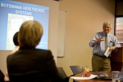 Max Essex (right), chair of the Harvard School of Public Health AIDS Initiative, and his colleagues believe that targeting those most likely to transmit HIV can greatly reduce disease incidence and be cost-effective.  HSPH researchers will use the grant to evaluate a unique combination of HIV prevention strategies in Botswana. In 2009, President Drew Faust (left) went to Gaborone, Botswana, to see the research being conducted there.