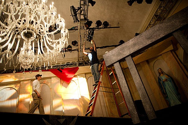 """A behind-the-scenes look at the Lowell House Opera. Stage manager Chad Andrew Burn (from left) and set designer Mark Buchanan prep the lighting before the dress rehearsal of Puccini's """"Tosca."""""""