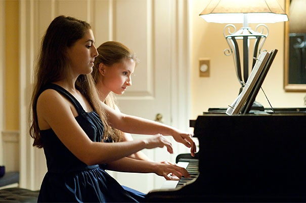 Twins Danielle '14 (left) and Arielle Rabinowitz '14 perform a piano duet before a black tie High Table dinner at Lowell House.