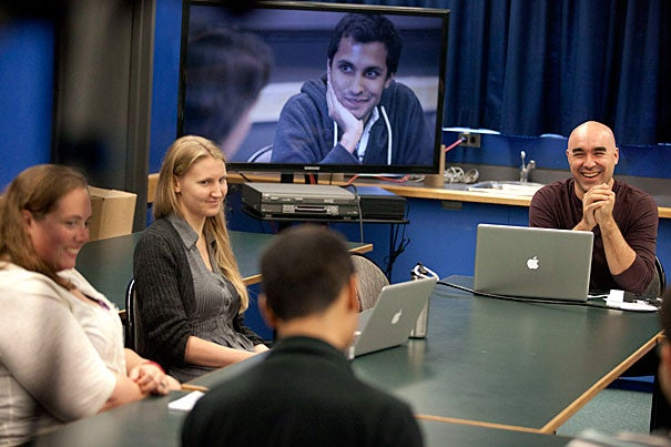 Bok Center coordinator Shelley Westover (from far left) and teaching fellow Anita Nikkanen join Bok Center Associate Director Marlon Kuzmick (shaved head) as he teaches a class about multi-modal communication and how it can be used in the classroom. GSAS health policy student Ankur Pandya is seen on the monitor practicing his teaching methods.