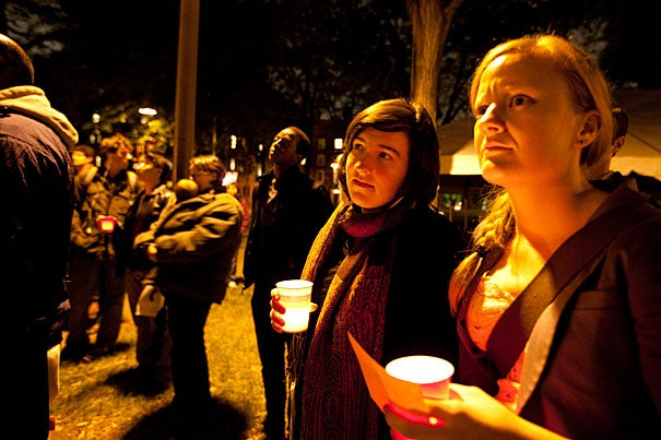 Divinity School students Julie Rogers (left) and Sierra Fleenor participated in a candlelight vigil the day after National Coming Out Day, when the BLGTQ and allied community at Harvard observed a moment of remembrance and reflection.