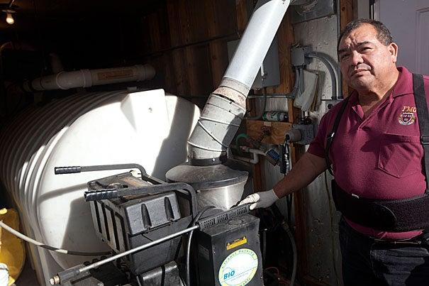Harvard staffer Miguel Espejo uses rain water to wash Harvard Shuttles. Harvard's Transportation Services reuses rainwater at 175 North Harvard St. to wash 250 University vehicles a week, saving 25,000 gallons annually.