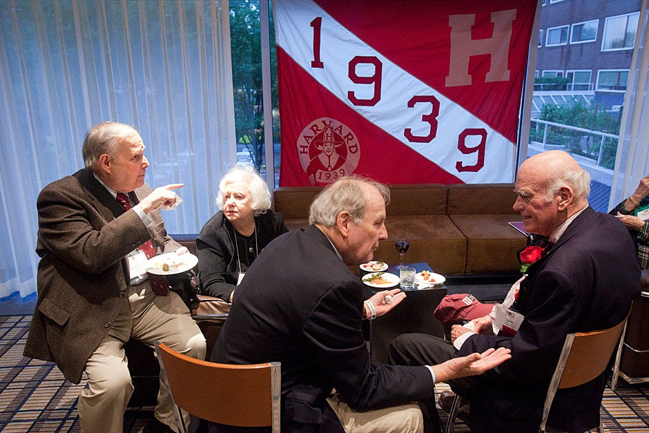 Mike Popernik '59 (from left), Frances Hill, Mal Hill '59, and Louis Newell '57 share stories beneath a 1939 banner at the alumni reception at the Charles Hotel. Jon Chase/Harvard Staff Photographer