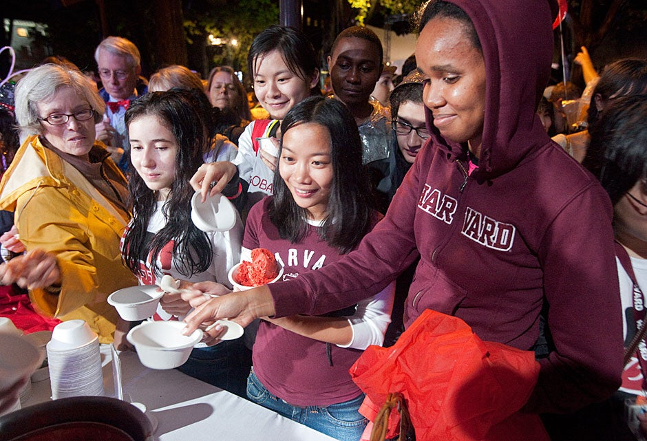 Anna Su (center) and Nkatha Kabira (right), both from Harvard Law School, reach for ice cream along with scores of other hungry participants.   Jon Chase/Harvard Staff Photographer