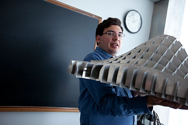 Joseph K. Blitzstein, a new professor of statistics and an award-winning teacher, holds a two-dimensional normal distribution built by Fred Mosteller, who founded the department in 1957. Bending it illustrates different correlations.