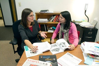 Nicole Newendorp (left) and her new Behavioral Laboratory in the Social Sciences (BLISS) research fellow Debra Chang look over  materials relating to a  summer research program at her office in Hilles.
