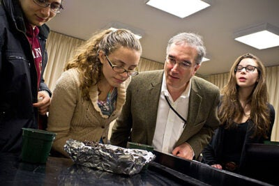 Earthworms took center stage at John Knowles Paine Hall last month as students in a freshman seminar re-created Darwin's experiment exploring the creature's hearing. Arnold Professor of Organismic and Evolutionary Biology Ned Friedman (third from left) and students peer at worms to see if they are responding to sounds, below, the stars of the show.