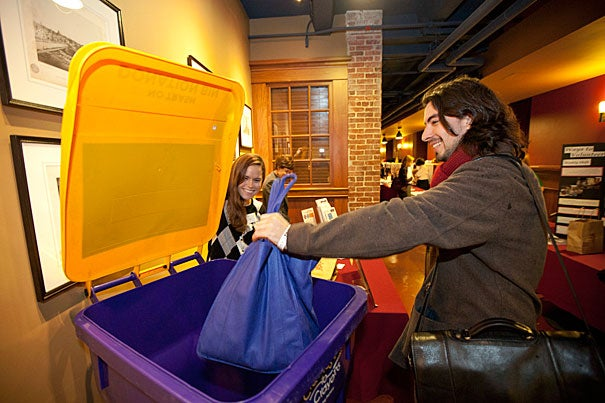 """Graduate School of Arts and Sciences student Antonio Arraiza Rivera (right) learned more about the Cradle to Crayons program, which serves children in need. Cradles to Crayons was among the organizations present for the  Community Gifts kickoff at Harvard. """"By joining together with others, we multiply the effect we have on our neighbors and communities,"""" said Katie Lapp, Harvard's executive vice president and co-chair of the 2011 Harvard Community Gifts campaign."""