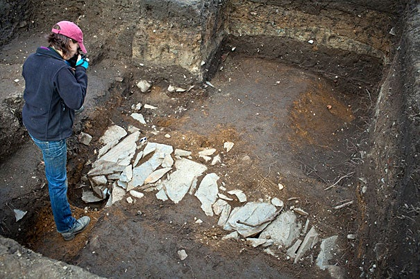"Christina Hodge takes photos where late last week students enrolled in ""The Archaeology of Harvard Yard"" uncovered what looked like a stone path."