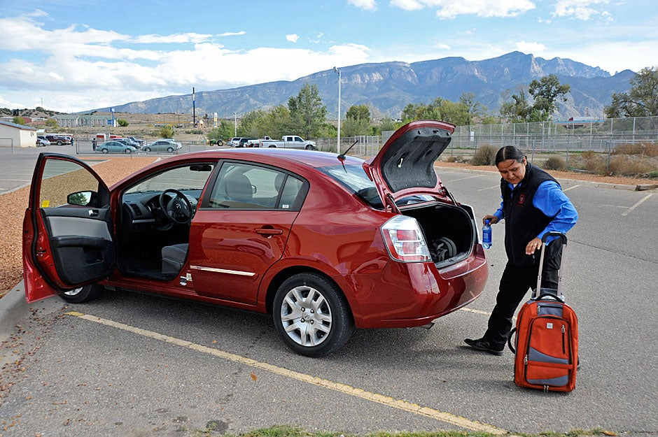 With the Sandia Mountains in the background, Jason Packineau loads a travel case packed with admissions literature into his car after a visit to Bernalillo High School. Jon Chase/Harvard Staff Photographer