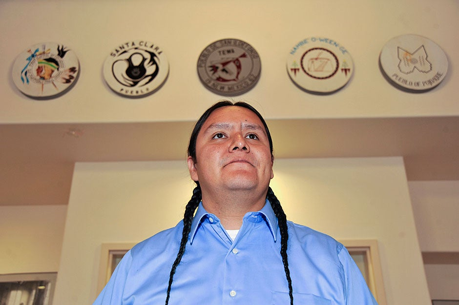 Against a backdrop of circular shields representing the pueblos of New Mexico, Jason Packineau prepares to address students at the Santa Fe Indian School. Jon Chase/Harvard Staff Photographer