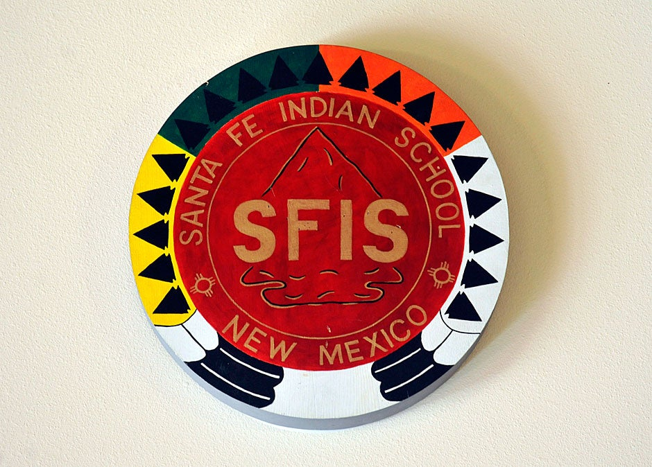 A seal on the wall of the Santa Fe Indian School overlooks a conference room where Jason Packineau presents college information to students. Jon Chase/Harvard Staff Photographer