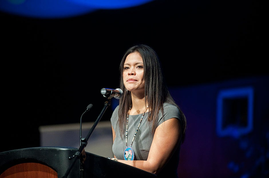 Mary Jane Oatman Wak-Wak, president of NIEA, addresses the National Indian Education Association conference. On a personal note, she spoke of the flood of feelings brought on by coming back to the place she calls home, her emotions underscoring her words as they briefly got the best of her. Coming home has special meaning for Native people, who are often torn at leaving their tight-knit communities for school or jobs where they feel cut off from their roots and traditions. Jon Chase/Harvard Staff Photographer