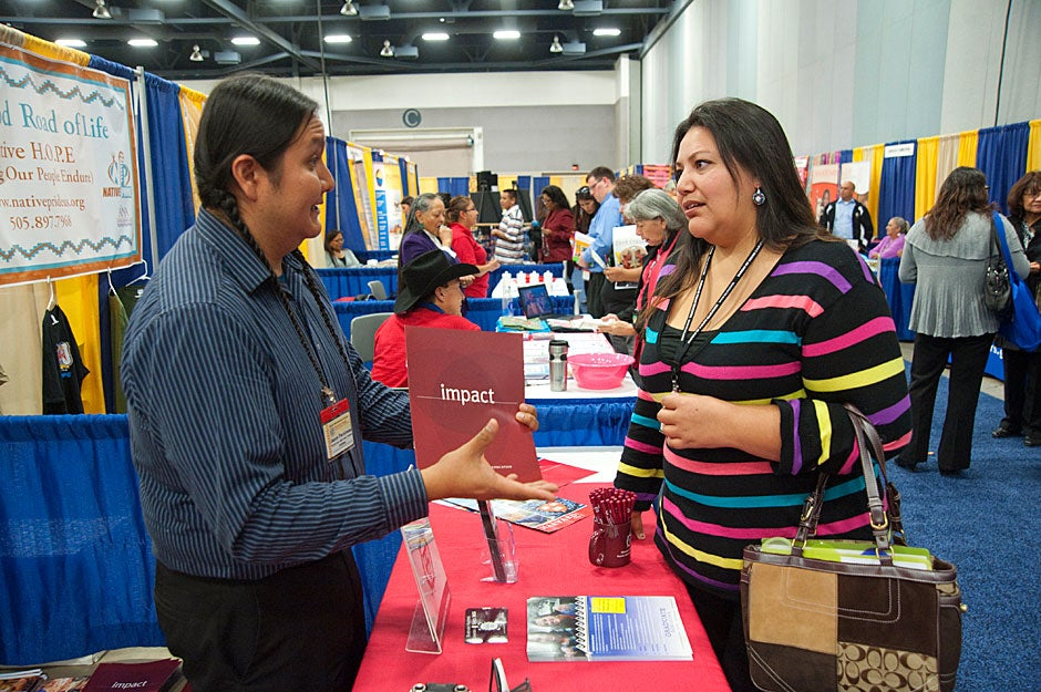 At the National Indian Education Association conference, Jason Packineau speaks with a woman inquiring about graduate school. Jon Chase/Harvard Staff Photographer