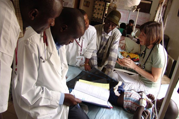 Sara Stulac (right), consults with colleagues at the Rwinkwavu Hospital in Eastern Rwanda. Stulac, who is a Harvard Medical School instructor in medicine and the director of pediatrics for Partners In Health, has designed a program that brings together Rwandan physicians with Boston-based pediatric oncologist.