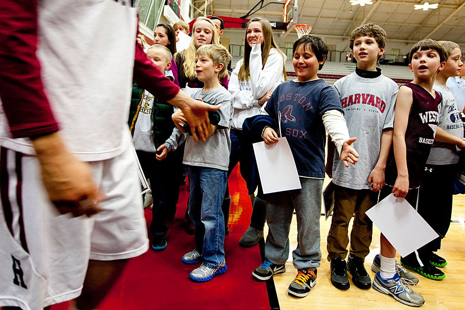A Harvard player gives a low-five to a young fan waiting in line to have a team photograph signed.  Rose Lincoln/ Harvard Staff Photographer
