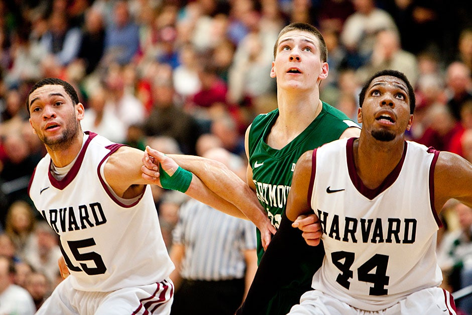 Harvard's Christian Webster (left) and Keith Wright squeeze out a Dartmouth player as all three vie for the rebound. Rose Lincoln/Harvard Staff Photographer