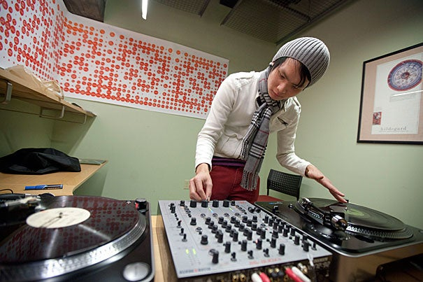 """Greg Yang '14 demonstrates his skills at the turntables after being shown the """"one-click flair,"""" a fast finger twitch method of isolating a single sound while spinning two records."""
