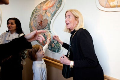 Artist Pam Ward (right) introduced her neighbor's granddaughter, Clara Marttila, age 5, to her art when collaborative murals were unveiled at Cambridge Health Alliance. Ward, and others, are part of the Ceramics Program at Harvard's Office for the Arts.
