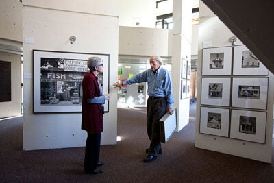 "Mather House Master Christie McDonald (left) discusses the latest exhibit with John T. Hill. Hill designed and produced ""Walker Evans: Before and After the FSA,"" which is on view at Mather House's SNLH Three Columns Gallery."