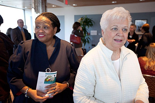 Four-year Chapman Arms resident Lynda Jordan (from left) and Ann Allosso, a 26-year resident, celebrate during the dedication ceremony for the Chapman Arms building in Harvard Kennedy School's Littauer Building.