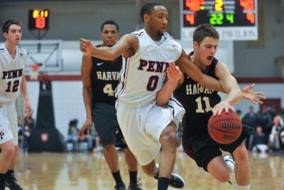 Harvard's Oliver McNally '12 (right) encounters some tough Penn defense as he drives toward the basket.