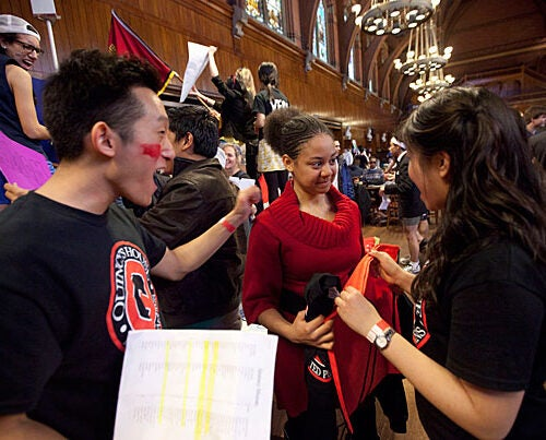 Camara Carter '15 (center) looks a little petrified by the Quincy House enthusiasm of Scott Yim '13 (left) and Lydia Chung '14.