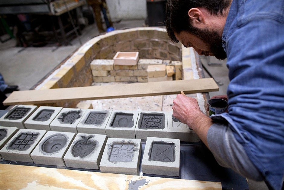 Students carved designs into resin-bonded sand blocks as an exercise in sand casting, one of two types of casting introduced during the workshop. Adam Stack, a graduate student in anthropology, brushes a graphite coating into his sand mold. Stephanie Mitchell/Harvard Staff Photographer
